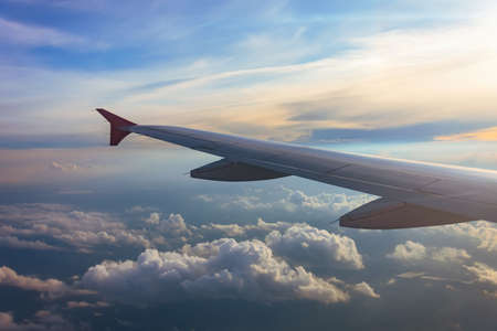 Wing of an airplane flying above the sunset clouds. Looks at the sky from the window of the plane, air travel Standard-Bild