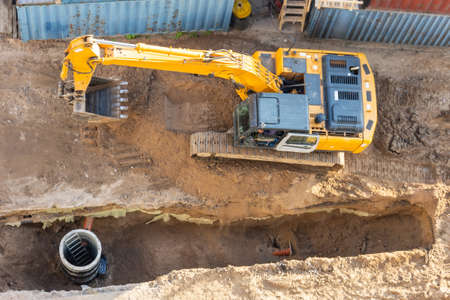 Excavator at a construction site while digging trenches for calcining sewer and drainpipes with a raised bucket, top aerial view