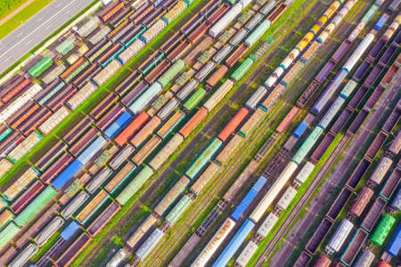 Cargo railway carriage. Colorful freight trains on the railway sort facility. Wagons with goods on railroad. Heavy industry, industrial scene