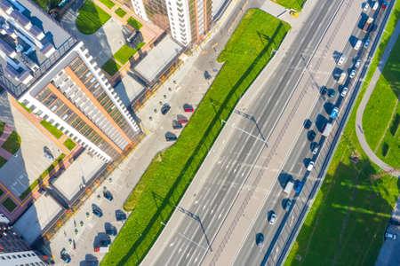 Urban highway car traffic jams with multi-storey buildings, aerial view
