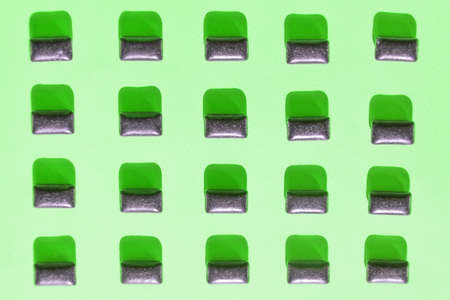 Black chewing gum pads on green background