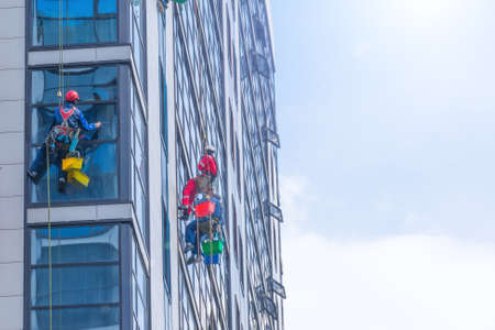 Outside of the building washing the glazing of the facade of a multi-storey building climbers clean windows, bottom view