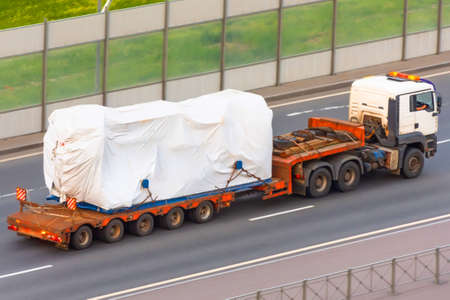 Truck with trailer and cargo covered with white cloth, tarpaulin. Rain protection