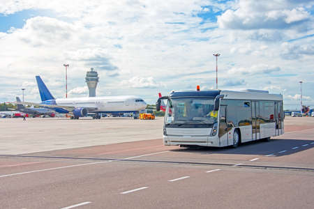 Bus for transporting passengers to boarding aircraft, against the background of a taxiing airliner on the apron of the airfield with a control tower