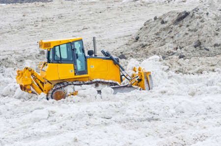 A huge amount of snow from city streets and cleaning it with a bulldozer