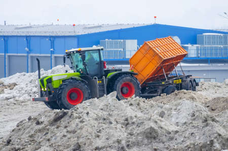 A powerful tractor with a trailer transports snow from city streets to snow-melting clusters of the installation
