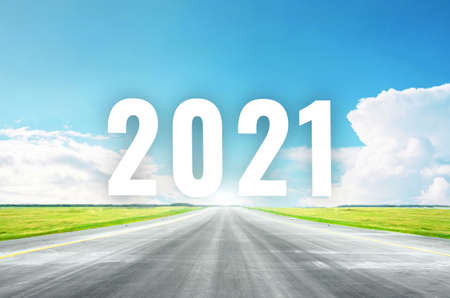 Numbers 2021 above the horizon on the road against the background of a light blue sky with clouds. Concept of approaching the new year