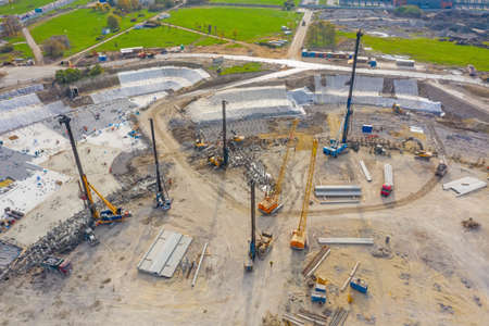 Equipment for installing piles in ground, heavy machines for driving pillars work in laying the foundation building. Construction aerial view height 写真素材