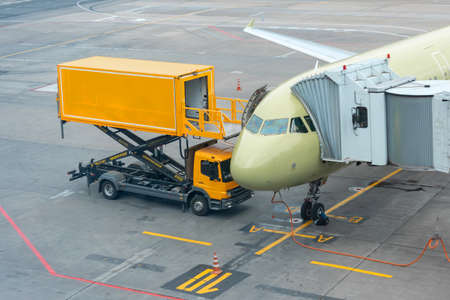 Yellow truck near to a passenger plane, pre-flight service airport Stock Photo