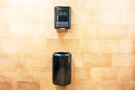 Paper towel black dispenser and a trash can at the bottom for used paper towels on the wall in a public toilet