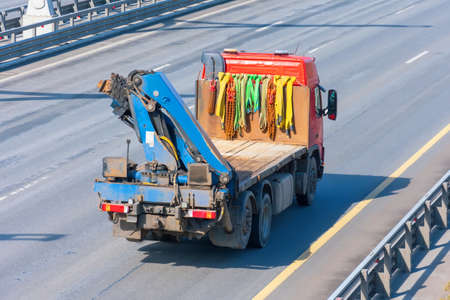 The small truck crane carries cargo on the highway