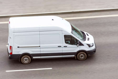 White minibus goes on the city highway street