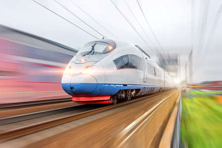 Electric train with glowing lights traveling at high speed