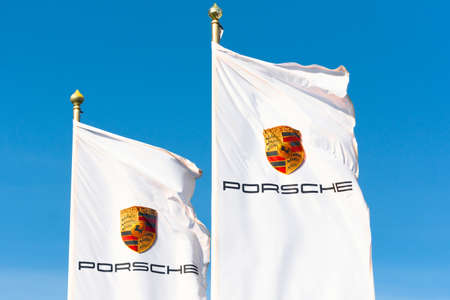 Two white flags with the Porsche car manufacturer corporation logo. Russia, Saint-Petersburg. 14 may 2020 Editoriali