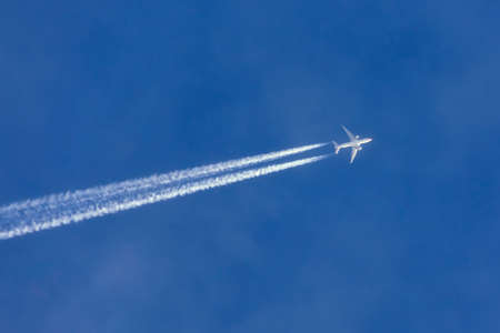 Airplanes leaving contrail trace turns in a clear blue sky