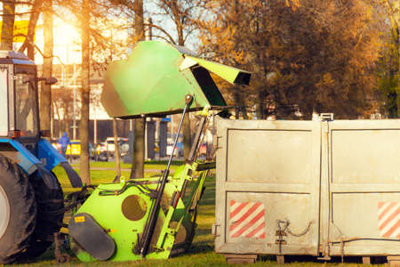 Vacuum sweeper towed by a tractor dumps into a container for harvesting leaves from city streets work in autumn park