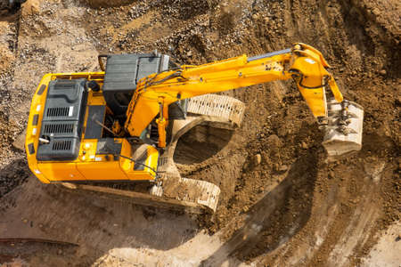 Excavator on the ground of a construction site with a raised bucket, top aerial view Archivio Fotografico