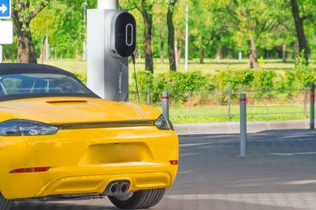 Electric car recharging parking lot, e-mobility. Hybrid engine gasoline and electricity repair shop service garage