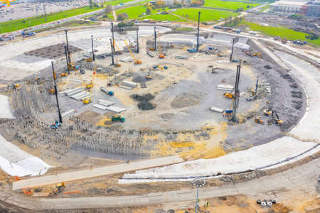 Construction of a stadium, exhibition complex, arena. Heavy machines for driving pillars work in laying the foundation building. Aerial view height