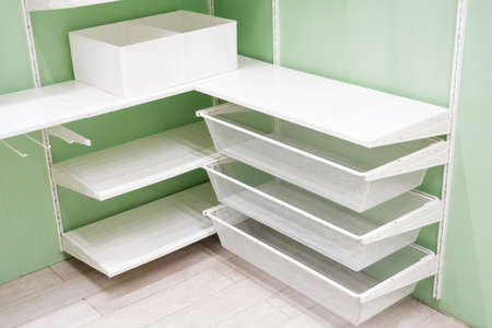 Empty white metal corner shelves for shoes in wardrobe, storage