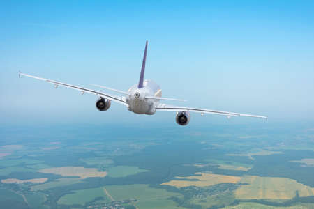 Airplane flying away into the distance in a clear sky not high above the earth's surface