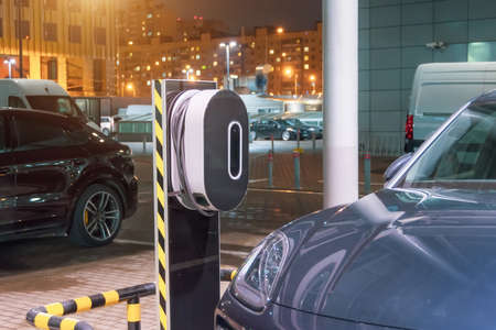 Night refueling in the city for electric cars e-mobility, the electric plug under voltage restores the battery charge Stockfoto