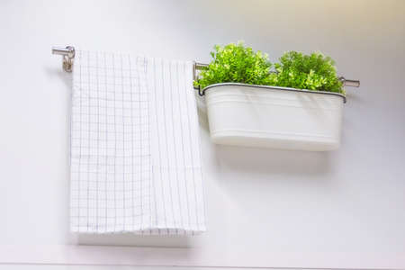 Cotton white towel with a square and strip pattern on the wall, next to a box with flowers