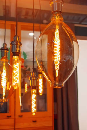Vintage lamps with a luminous LED spiral in the form of bulbs, ovals and drops in a retro interior 免版税图像