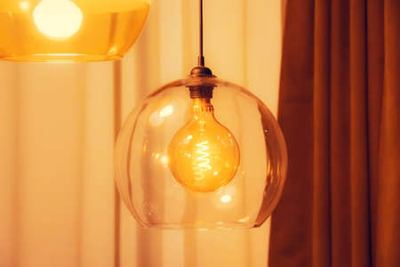Retro style lamp inside electric spiral in warm light in double glass
