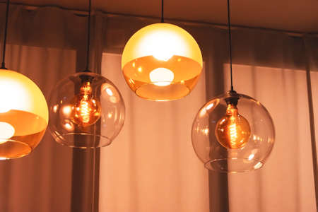 Several lamps in a retro style inside an electric spiral in warm light in double glass suspended above the table 免版税图像