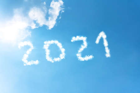 Numbers 2021 symbol inscription on a background of blue sky from white smoke of clouds lit by a bright sun