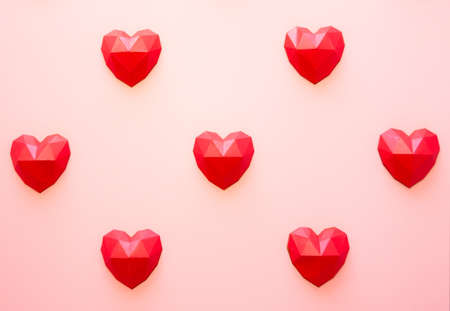 Holiday background for Valentine's Day, Red polygonal paper heart shapes on a cream background. Love concept. Plain. Minimalistic style 版權商用圖片
