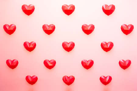 Holiday background for Valentine's Day, Red polygonal heart shapes on a cream background pattern. Love concept. Plain Minimalistic style