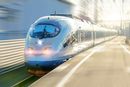 Electric passenger train drives at high speed departs from the platform