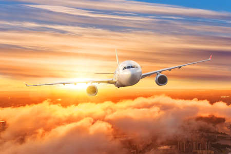 Airplane above the clouds in the sky at sunrise Standard-Bild