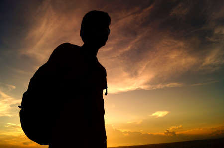 undertaking: silhouette of a guy with a bag undertaking a journey alone Stock Photo