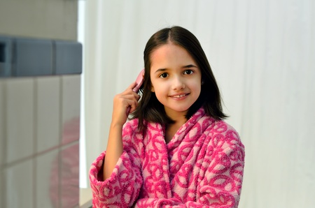 Little Hispanic Girl Brushing her Hair Stock Photo