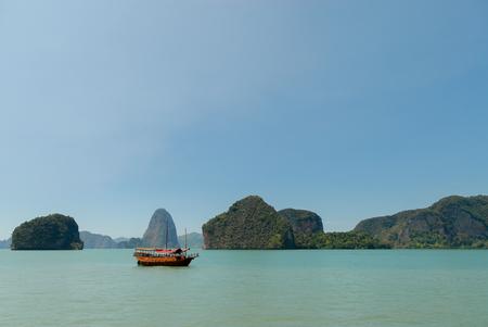 Wooden boat near limestone islands in the sea in Thailand Stock Photo