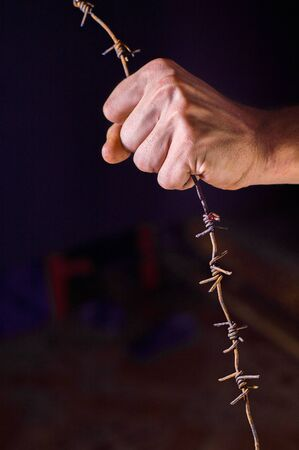 hand holds rusty barbed wire