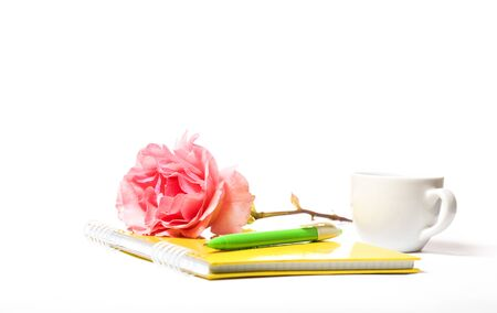 yellow notebook rose and pen on a white background