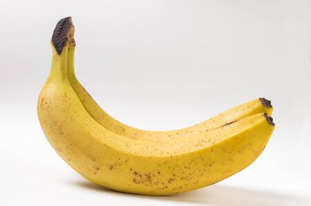 Dos plátanos maduros sobre un fondo blanco. Foto de archivo