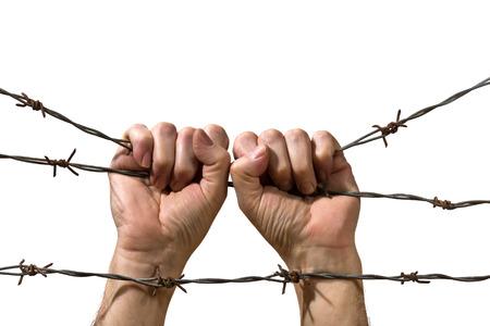 prisoner of war: hands behind barbed wire