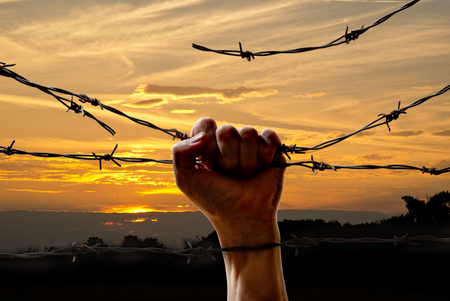 wire fence: hand behind barbed wire with sunset in the background Stock Photo