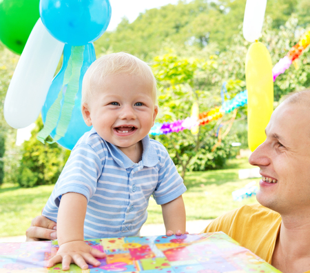 young family celebrated birthday in the garden photo