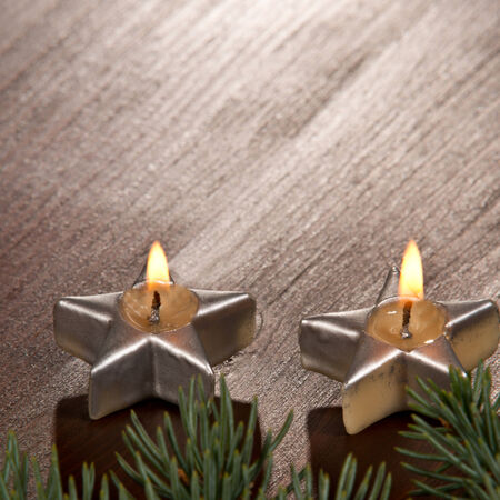 two Christmas candles with twig on the desk photo