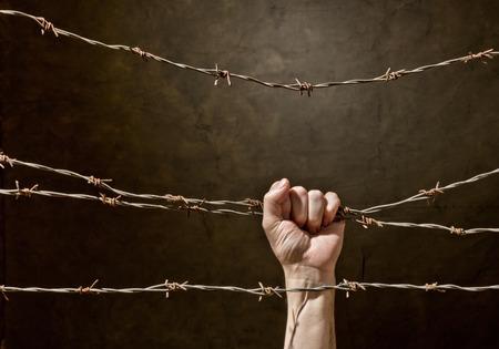 hand behind barbed wire with dark background photo
