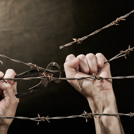 wire fence: old rusty barbed wire with hand on the dark background Stock Photo