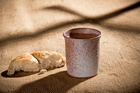 COMUNION: cáliz y pan sobre el mantel textil Foto de archivo