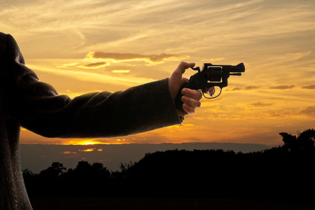 silhoutte of a man with a handgun at sunset photo