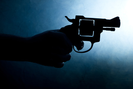 Silhouette of a mans hand with a handgun in blue